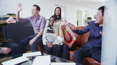 stock-footage-happy-mixed-ethnicity-team-of-young-professionals-are-seated-around-a-coffee-table-and-holding-an